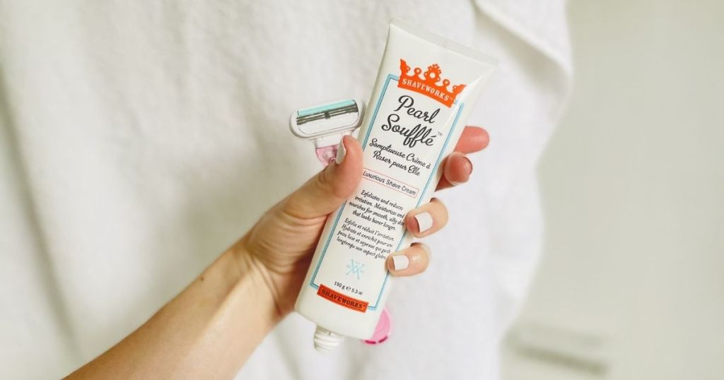 hand holding Shaveworks shaving cream and pink razor