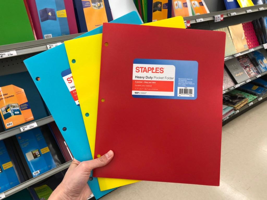 hand holding three folders