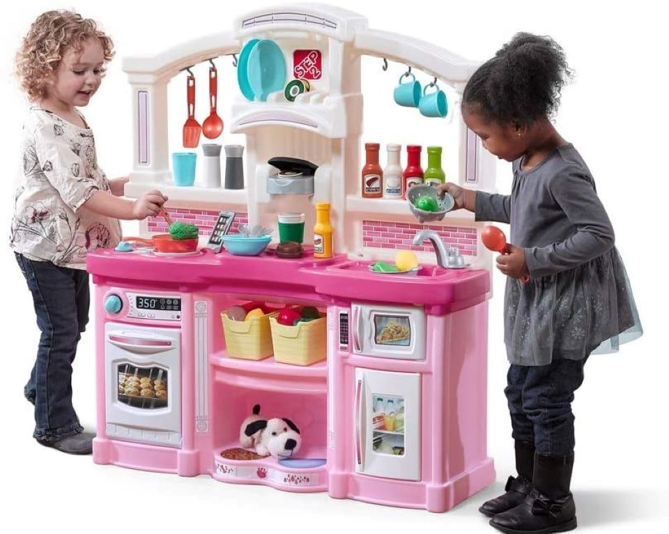 two girls playing with a toy kitchen