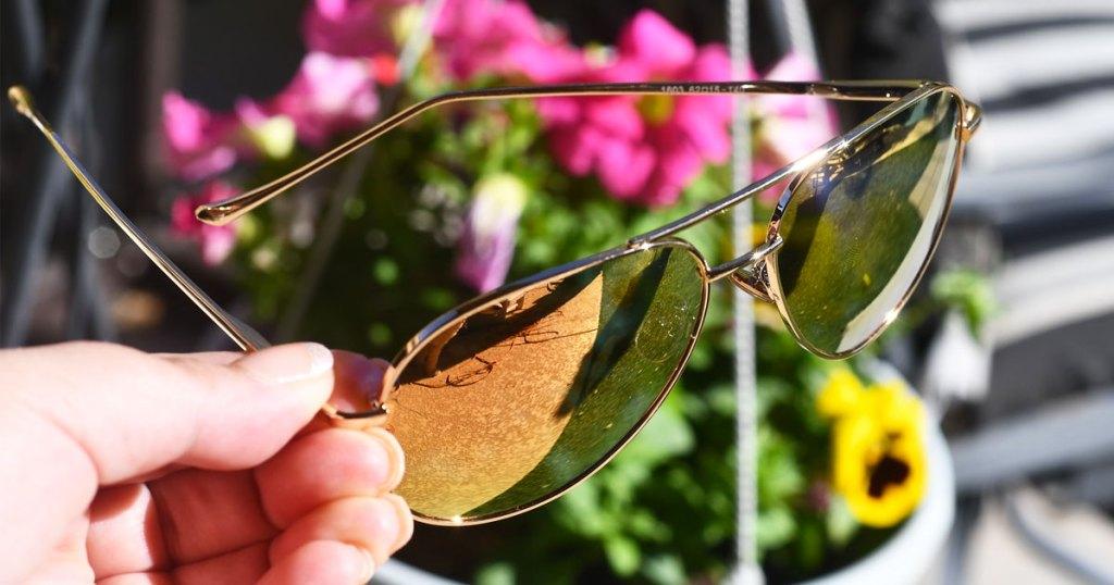 holding pair of aviator sunglasses