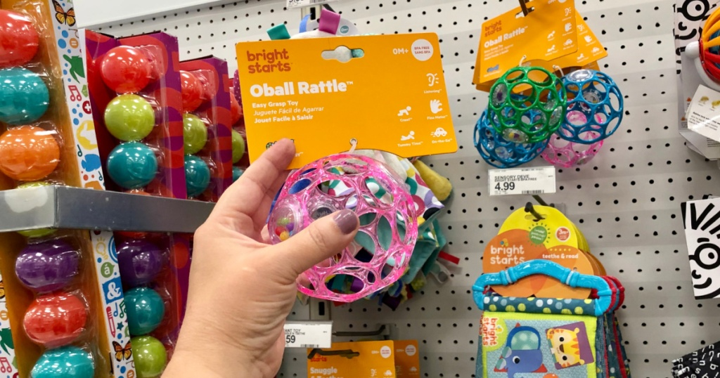 hand holding a toy ball for babies near in-store display