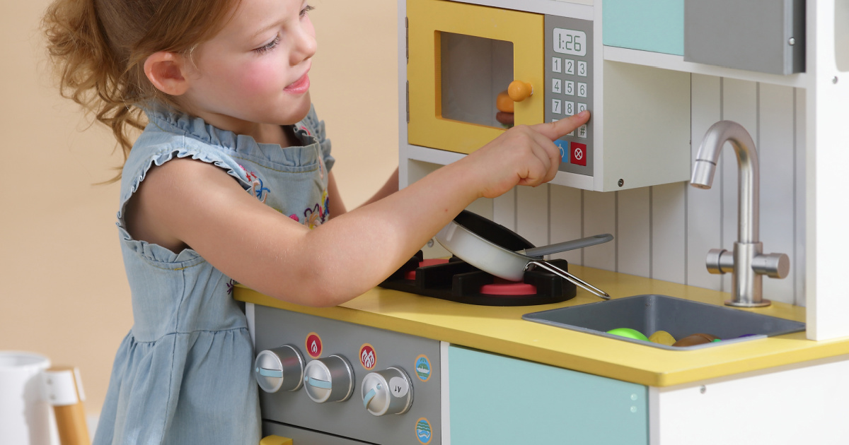 girl playing with a kitchen playset