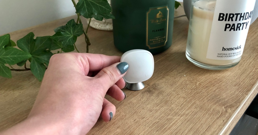 Hand holding a thermostat sensor