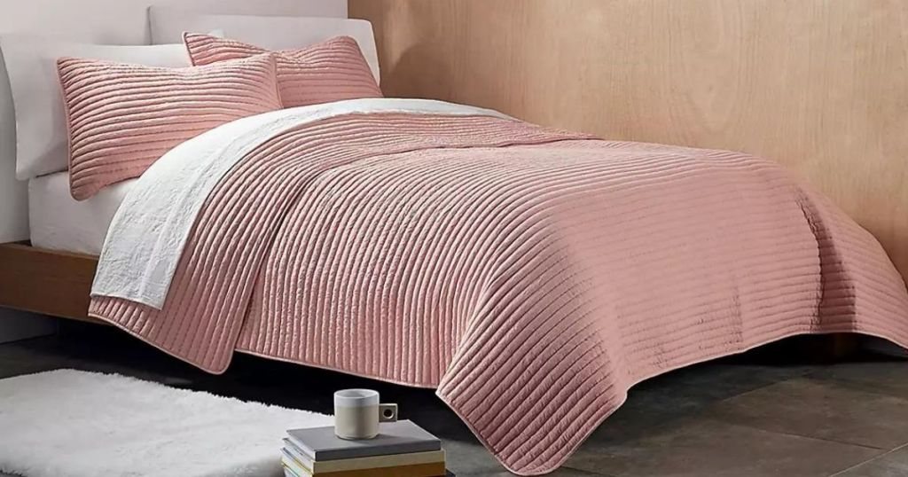 bed with a pink blanket on it