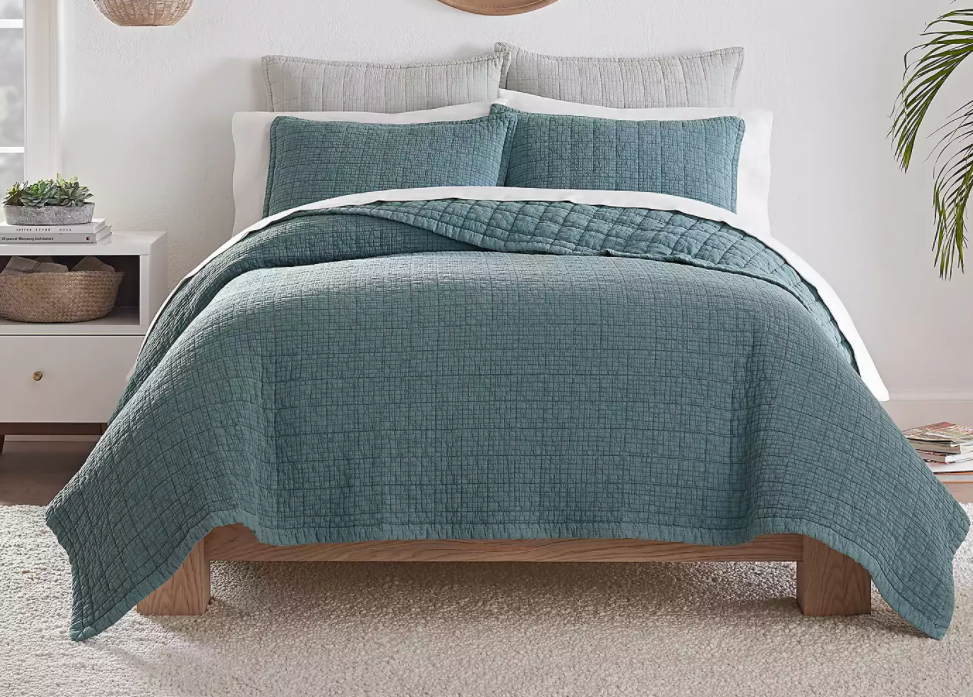 bed with a teal blanket and pillows