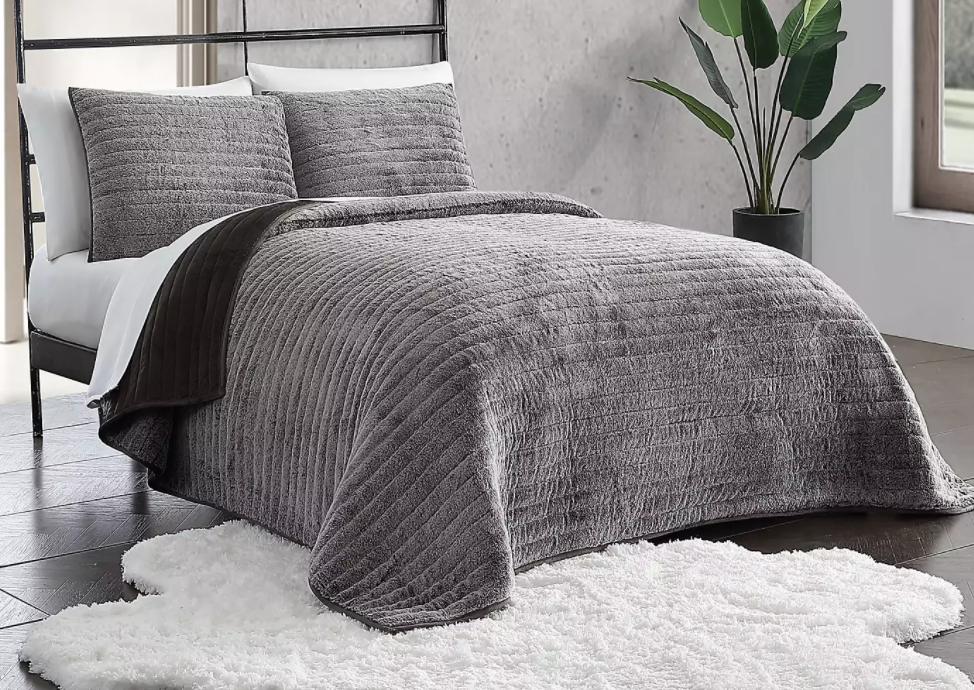 grey quilt and pillows on a bed