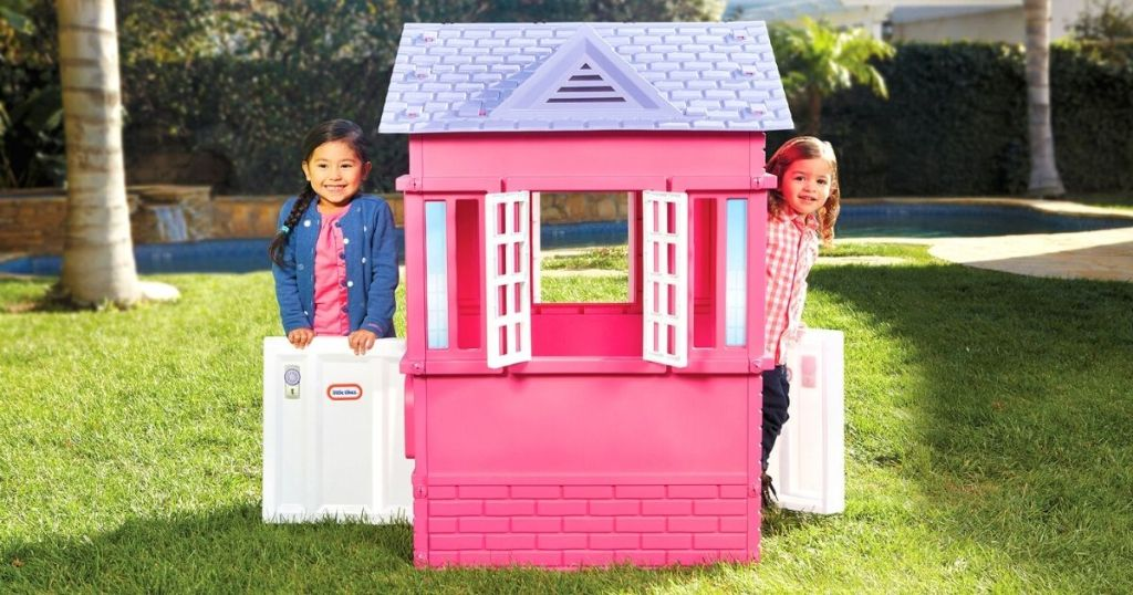 Little tikes playhouse with two little girls looking outside the window
