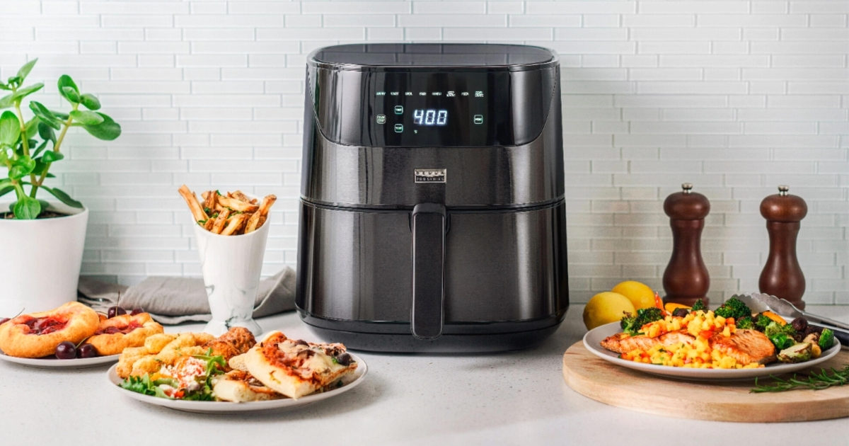 black air fryer on kitchen counter with plates of food around it