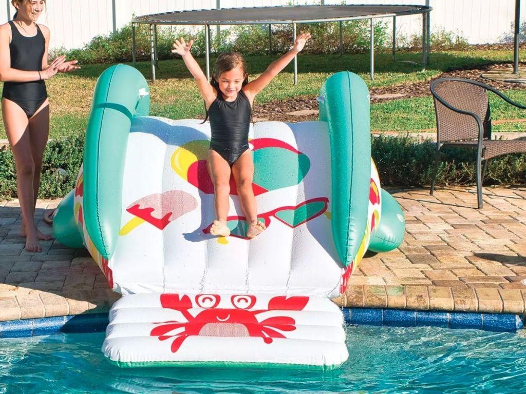 little girl sliding down inflatable pool slide