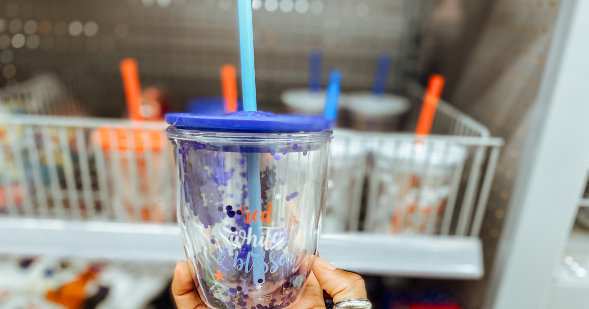 hand holding a red white and blue cup with straw