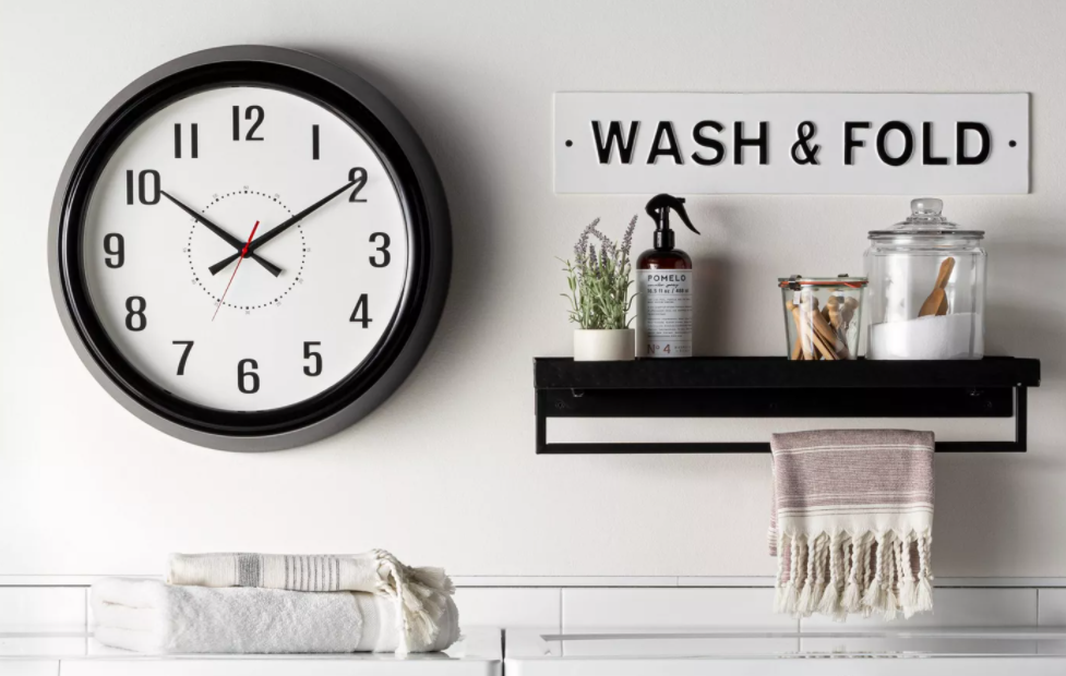wall with a clock, sign and storage shelf