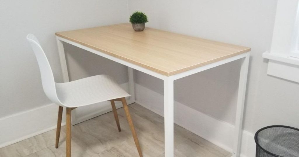 desk with a white chair and a small plant on it