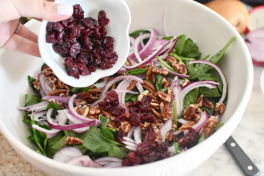 adding dried cherries to spinach salad