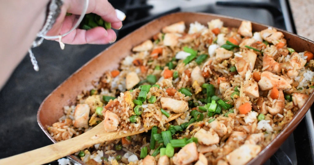 adding green onion to fried rice