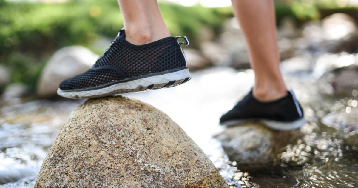 child stepping on rock in water shoes