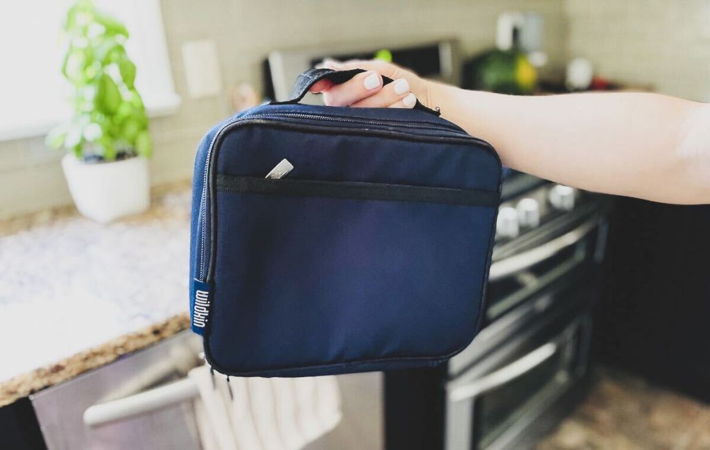 hand holding up navy blue lunchbox in kitchen