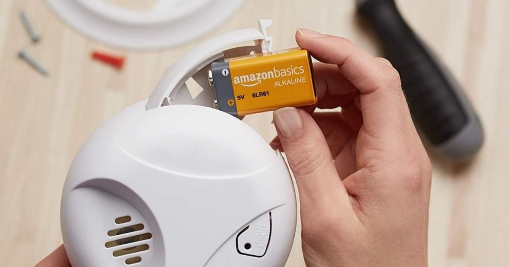 hand putting Amazonbasics batteries in smoke detector