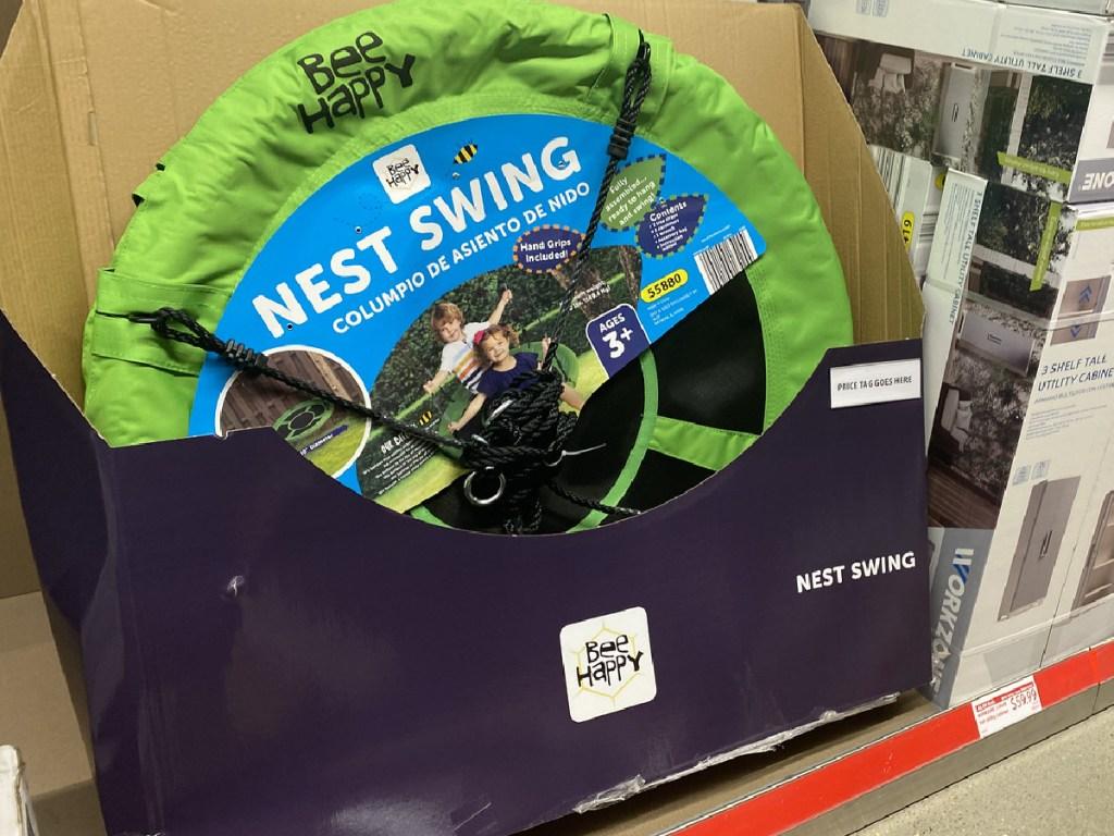 large green mesh swing that kids sit on at store display
