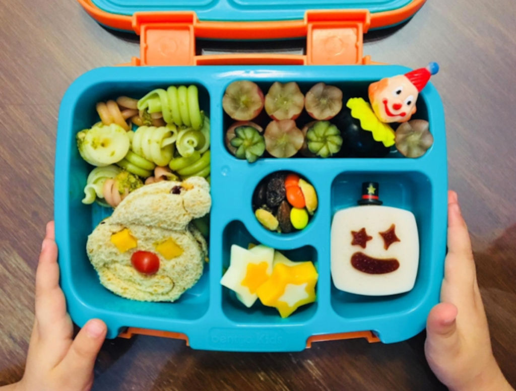 kids hands holding sides of blue organized lunchbox