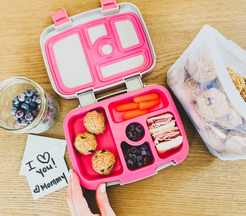 hand holding corner of open pink kids lunchbox with food in each compartment