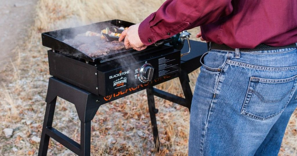 man using flat top grill