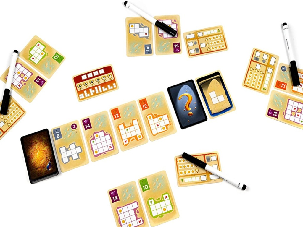 silver and gold card game displayed with dry erase marker