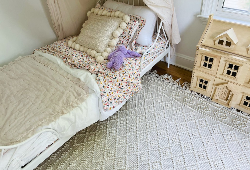 corner of kids bedroom with boho knotted rug and bed with flowers and pillow