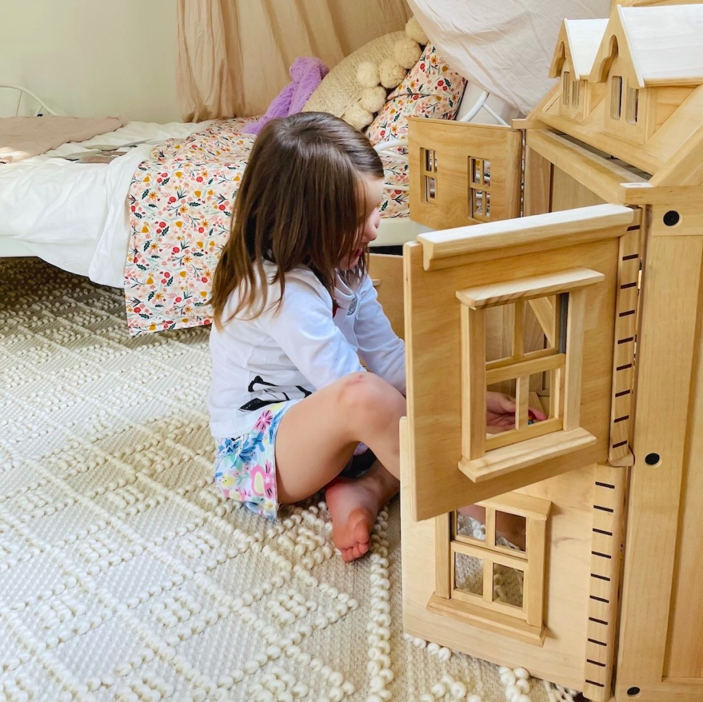 girl playing on rug with wooden dollhouse