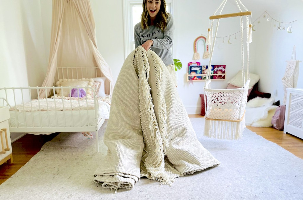 woman holding large rolled cream rug in kids room