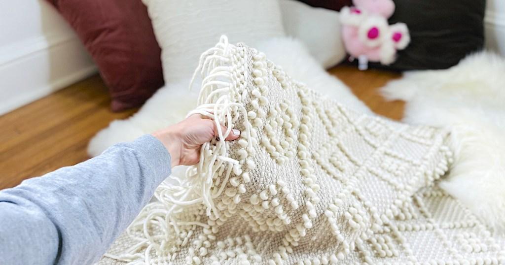 hand holding corner of boho tassel rug