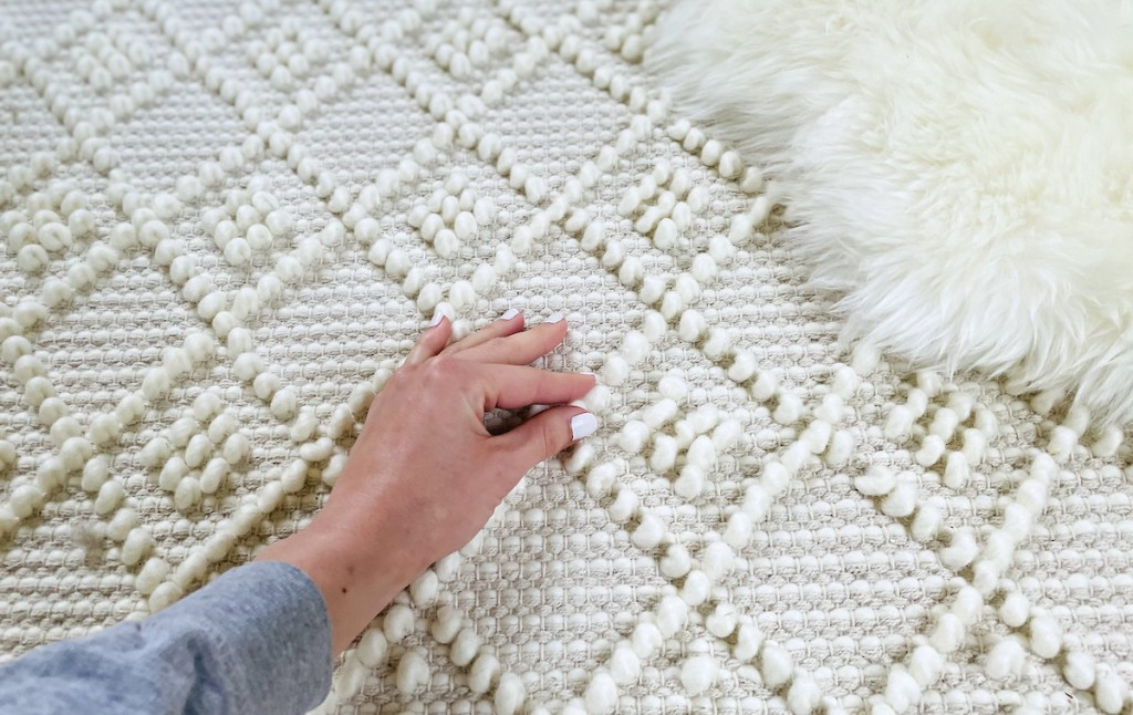 hand touching surface of knotted boho cream rug