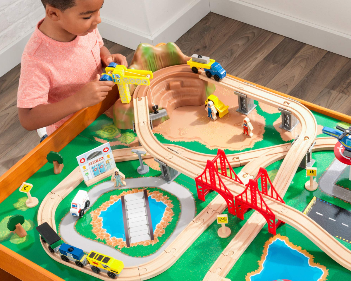 boy playing with kidkraft train table
