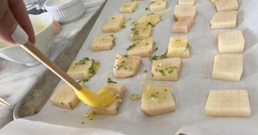 brushing parmesan oil on potatoes