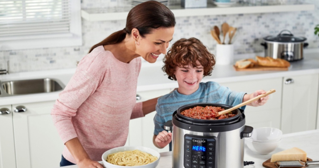 woman and boy cooking on a crock pot