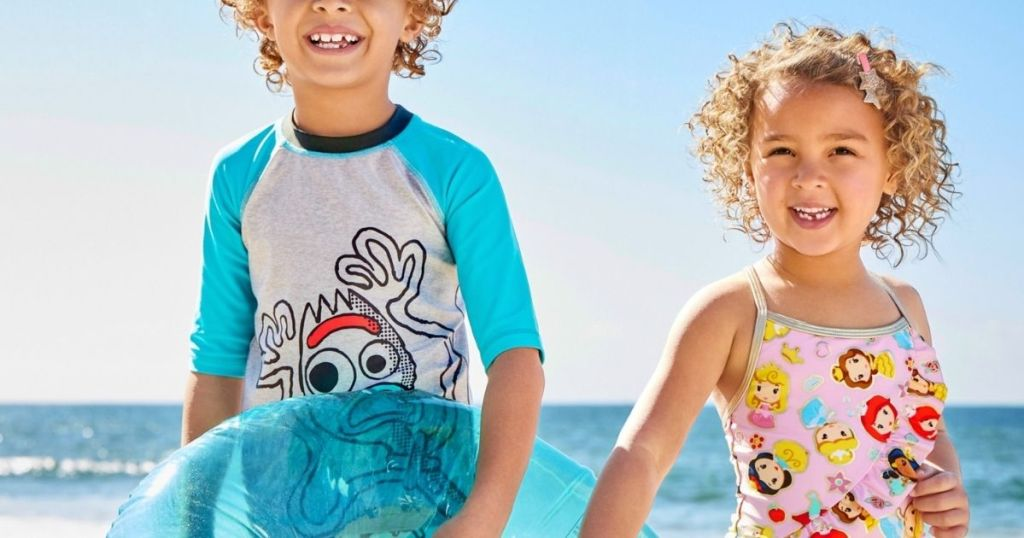 boy and girl wearing Disney swimsuits at the beach