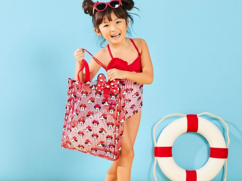 girl wearing Minnie one-piece swimsuit holding Minnie tote bag