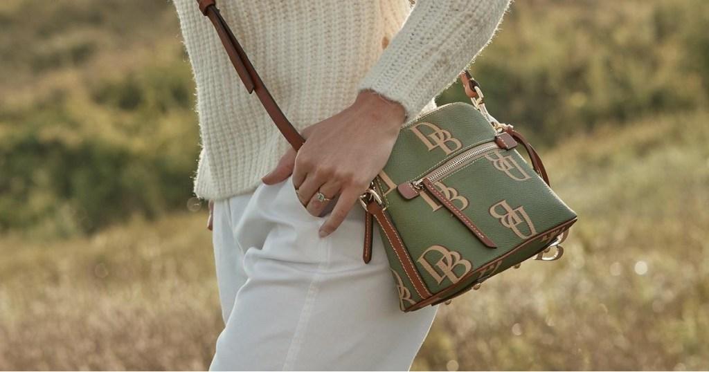 woman's body carrying purse in field