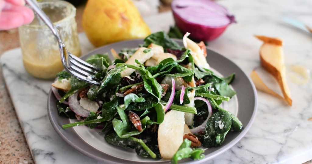 eating a pear and spinach salad