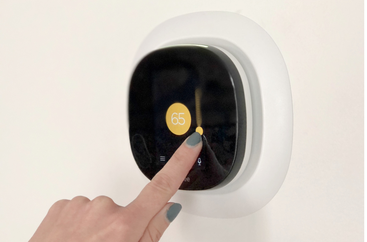 woman pressing a button on a smart thermostat
