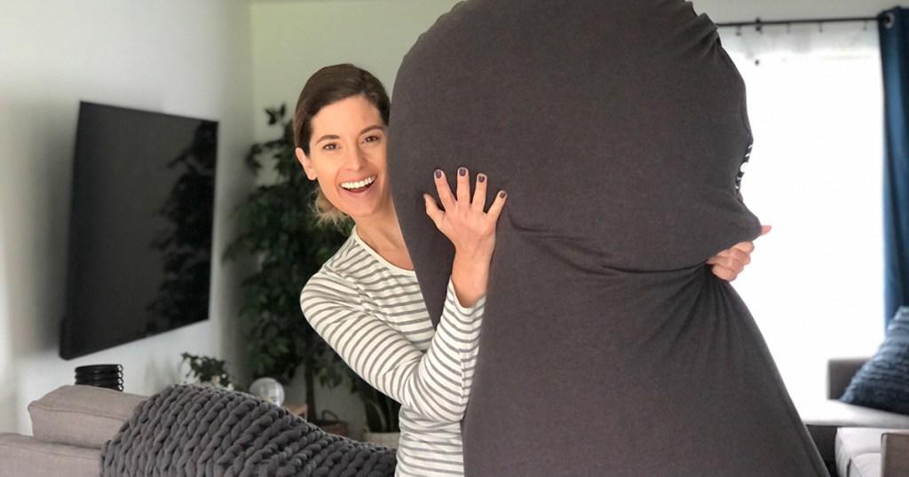 woman holding mood pod bean bag chair smiling