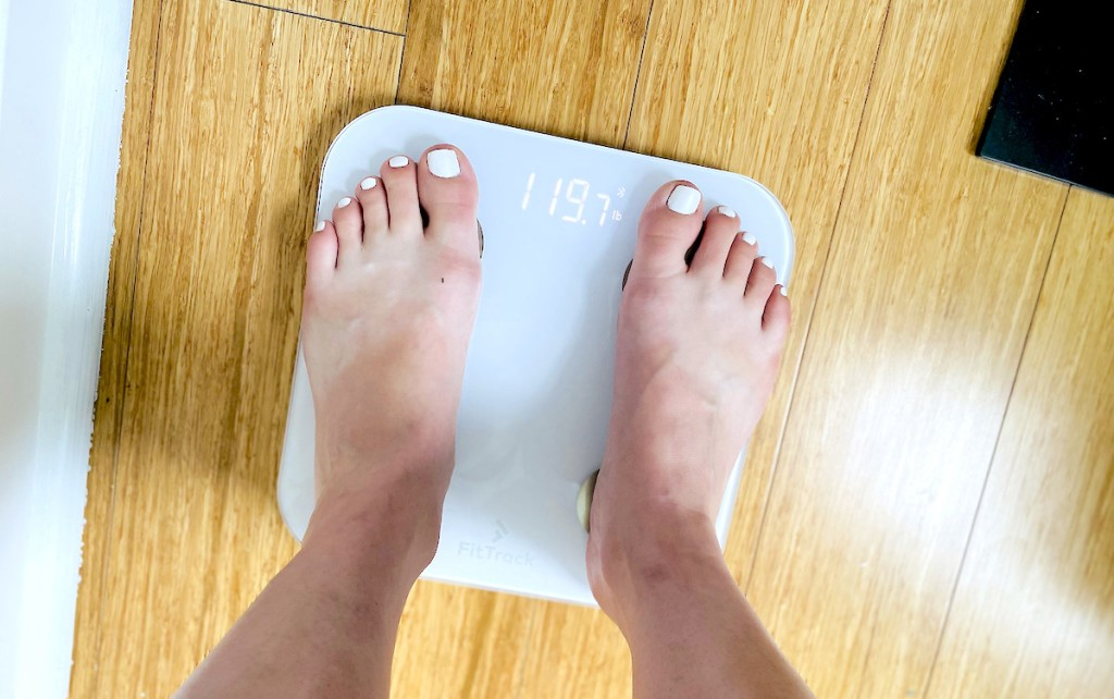 feet standing on top of white scale with weight at the top