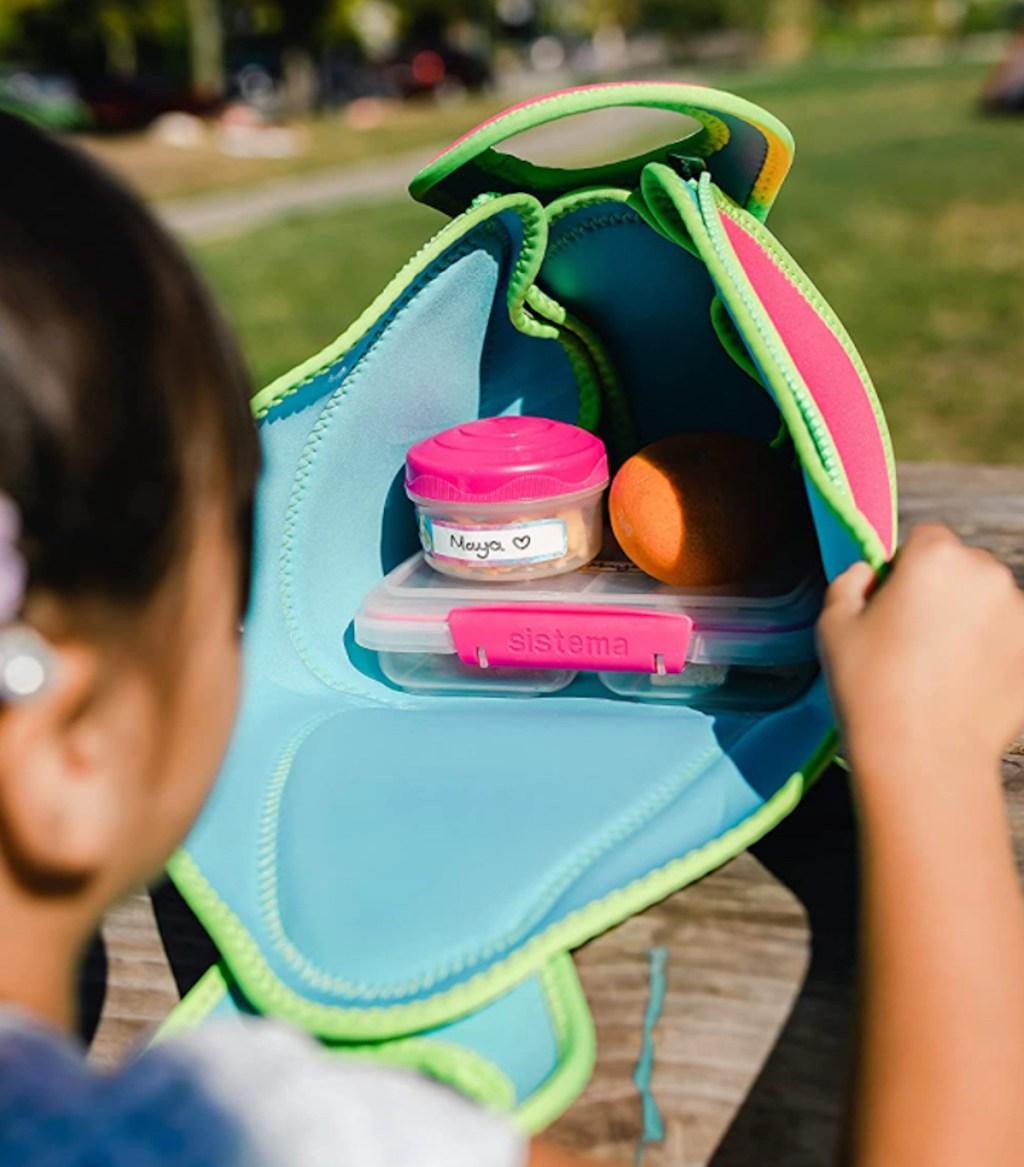 child peeking into open lunchbox
