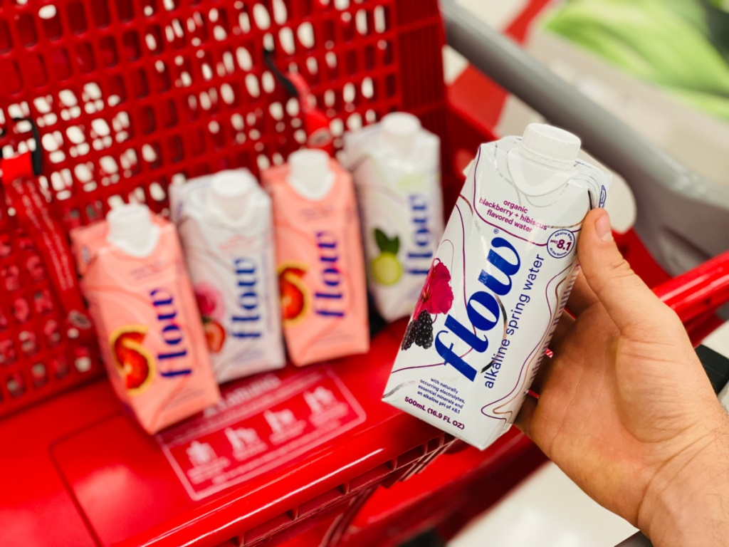 hand holding carton of alkaline water by red grocery cart
