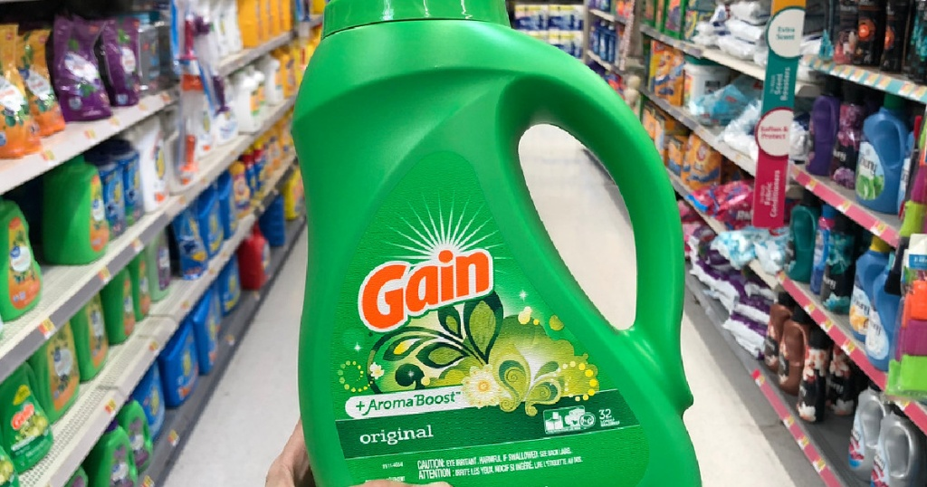 hand holding bottle of gain laundry detergent in store