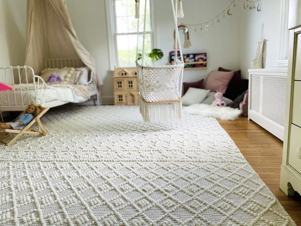little girls bedroom with cream boho area rug