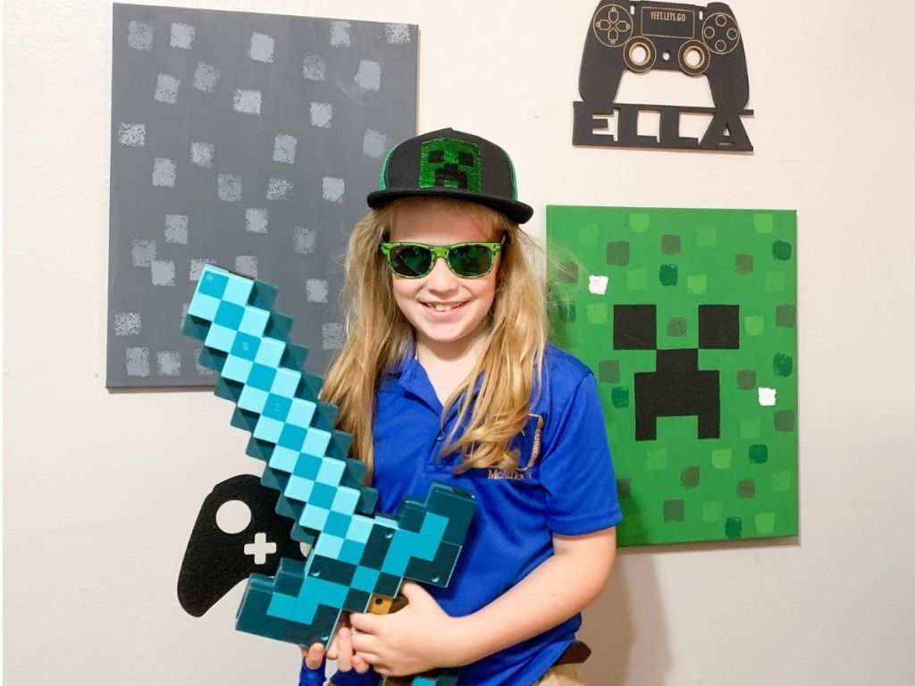 girl wearing Minecraft gear standing in front of Minecraft wall decor