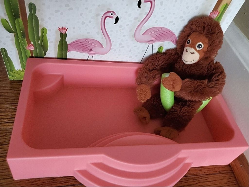 toy plush monkey sitting on pool noodle in toy pool