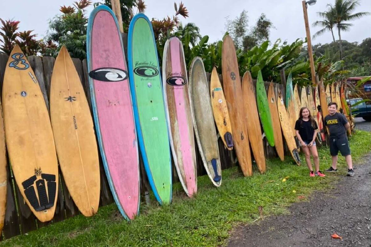 hawaii vacation surf boards lined up on side of the road beside two kids