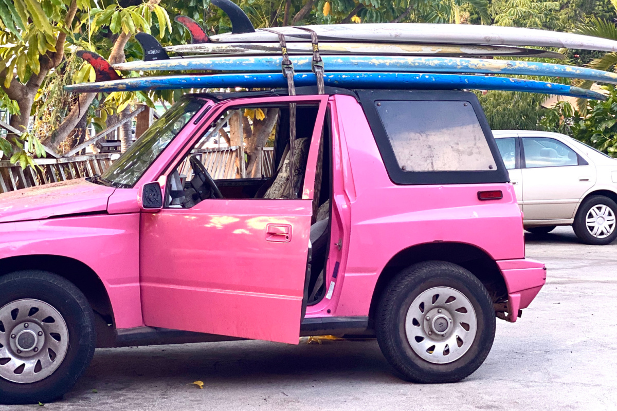 pink jeep with surfboards on top on hawaii vacation