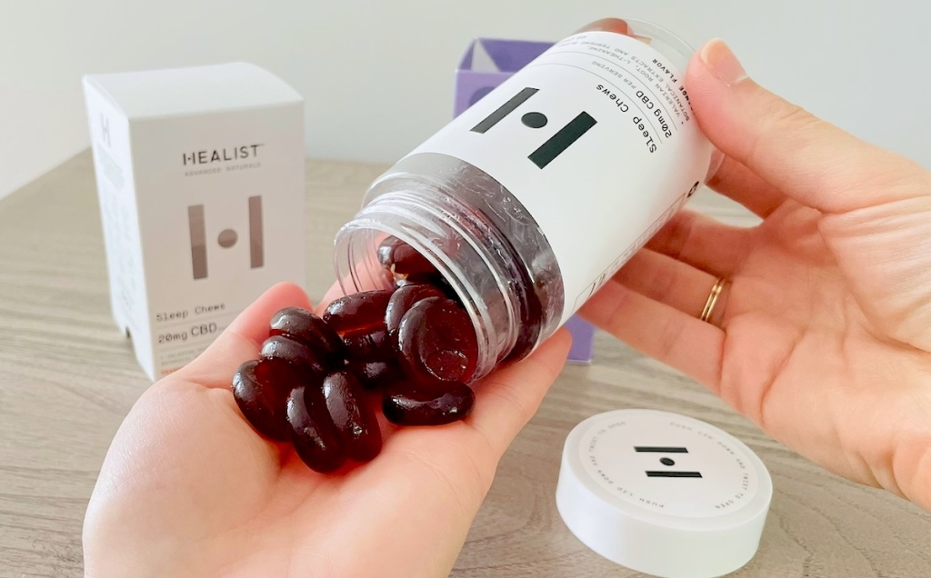 hand holding bottle of cbd sleep chews pouring out into hand
